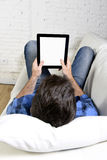 Man lying on home couch using digital tablet pad in portable internet technology. Man lying on living room couch enjoying at home using digital tablet pad in Stock Photo