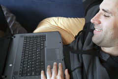 Man lying at home with a laptop Stock Images