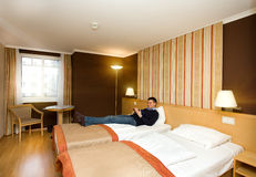 Man lying in hotel room. Young attractive man lying in hotel room and reading a book Stock Photos