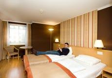 Man lying in hotel room Stock Photos