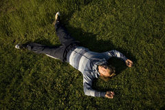Man lying on a lawn stock image