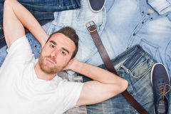 Man lying on many jean clothes. Cenital photo Royalty Free Stock Image