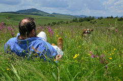 Man Lying on Meadow with His Dog Royalty Free Stock Photos