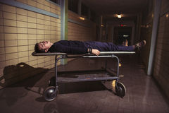 Man lying on medical patient stretcher in old horror hospital Royalty Free Stock Photo