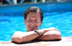 Man Lying On Side Of Swimming Pool In The Sun Stock Photo