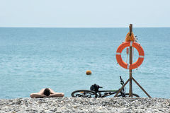 A man lying on the pebbly beach next to lifeline. And the bike Stock Photo