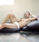 Man lying on pillows stock photo