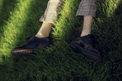 Man lying and relaxing on the grass. Legs, top view.  Pair of male legs in shoes lying on green grass. Very fashionable shoes. Photo for shoe store. Sale stock image