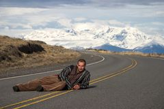 Man lying on the road with the mountain behind stock photo