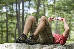 Man lying on a rock reading a book Stock Photography