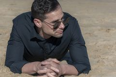 Man lying on the sand on the beach. With a black shirt, sunglasses and a few days` beard Stock Photography