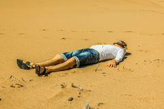 Man sleeping. A man with hat, jeans shorts and sweatshirt resting sleeping on the desert sand. Concept of calm, serenity and peace Stock Photo
