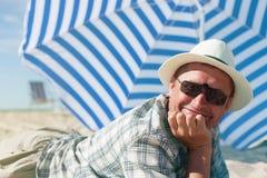 Man lying sand summer beach umbrella happy smile Stock Photos