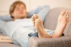 Man lying on sofa Stock Images