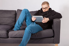 A man lying on a sofa and has a tablet PC in his hands. A young man lying on a sofa and has a tablet PC in his hands Stock Photography