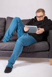 A man lying on a sofa and has a tablet PC in his hands. A young man lying on a sofa and has a tablet PC in his hands Royalty Free Stock Photos