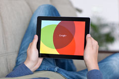 Man lying on the sofa and holding iPad with App Google on the sc Stock Photo