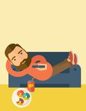Man lying in the sofa holding a remote Royalty Free Stock Photography
