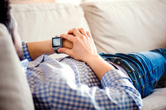 Man lying on sofa at home using smart watch Royalty Free Stock Photo
