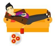Man lying on sofa with junk food. Stock Photo