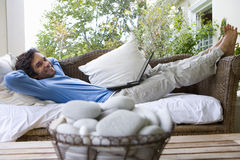 Man lying on sofa with laptop on lap, smiling, portrait, bowl of pebbles in foreground (differential focus) Stock Photo