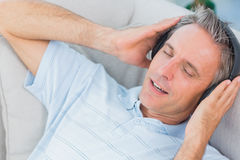 Man lying on sofa listening to music with eyes closed Royalty Free Stock Photo