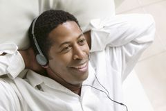 Man lying on sofa Listening to Music on portable CD player close up overhead view Royalty Free Stock Images
