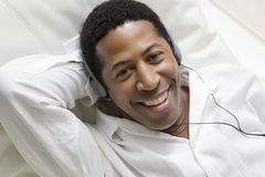 Man lying on sofa Listening to Music on portable CD player portrait overhead view Stock Image