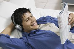 Man lying on sofa Listening to Music and Reading Magazine high angle view Royalty Free Stock Photo