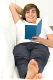 Man lying on sofa, reading Stock Photos