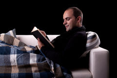 Man lying on the sofa reading a book, Stock Image