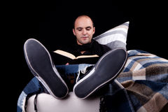 Man lying on the sofa reading a book, Stock Photo