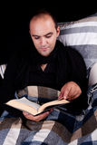 Man lying on the sofa reading a book Stock Image