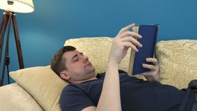 Man is lying on sofa and reading book. stock footage