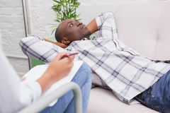 Man lying on sofa talking to his therapist Stock Photo