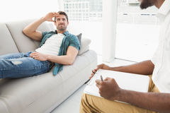 Man lying on sofa talking to his therapist Stock Image