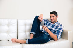 Man lying on the sofa and using smartphone Royalty Free Stock Images