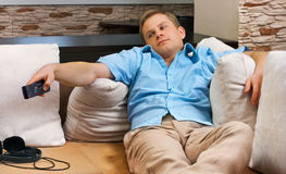 Man lying on sofa watching TV at home. This is man lying on sofa watching TV at home stock photography