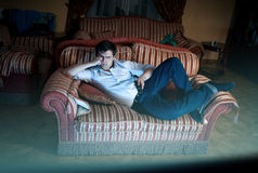 Man lying on sofa and watching TV at night Royalty Free Stock Photography