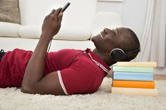 Man Lying On Stack Of Books Listening Music Royalty Free Stock Photography