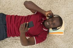 Man Lying On Stack Of Books Listening Music On Headphones. High Angle View Of African Man Listening Music Or Audiobook Royalty Free Stock Photography