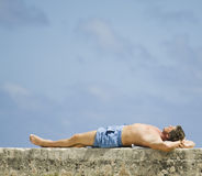 Man lying in the sun. Man on vacation resting and enjoying the sun. Room for text Royalty Free Stock Photo