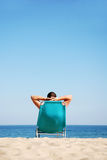 Man lying on sunbed. A man with arms behind head relaxing on blue sunbed Stock Photo