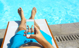 Man lying on sunbed near pool with phone. Summer vacation Stock Photos