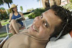 Man Lying on sunlounger Listening to headphones portrait. Royalty Free Stock Photography
