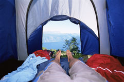 Man lying in tent with a view of lake Stock Photos