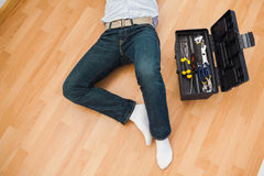 Man lying with a tools box near him Royalty Free Stock Images