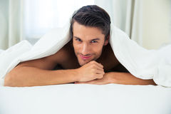 Man lying under blanket in the bed Royalty Free Stock Photography