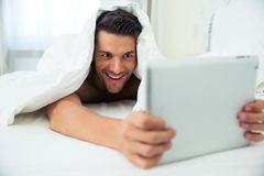 Man lying under blanket and using tablet computer Stock Images