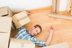 Man lying under fallen boxes Royalty Free Stock Photos